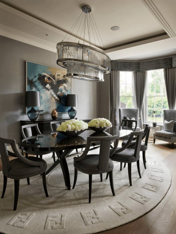 Luxury dining room boasts a black dining set on a round textured rug and a pair of high back chairs by the full height windows dressed in gray draperies. It is illuminated by a captivating chandelier that hung from the tray ceiling.