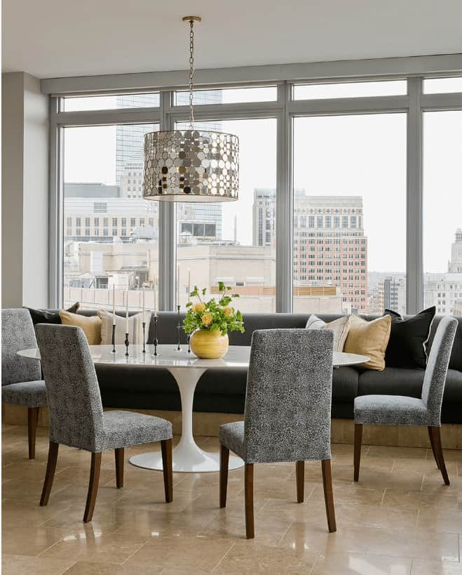 Contemporary dining room with marble tile flooring and glass paneled windows framing an incredible city view. It has a white dining table paired with upholstered chairs and built-in bench fitted with gray cushions.