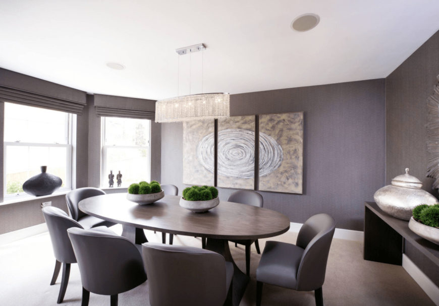 Sleek dining room designed with linear crystal chandelier and multi-panel wall arts mounted across the oval dining set that's paired with gray modern chairs.