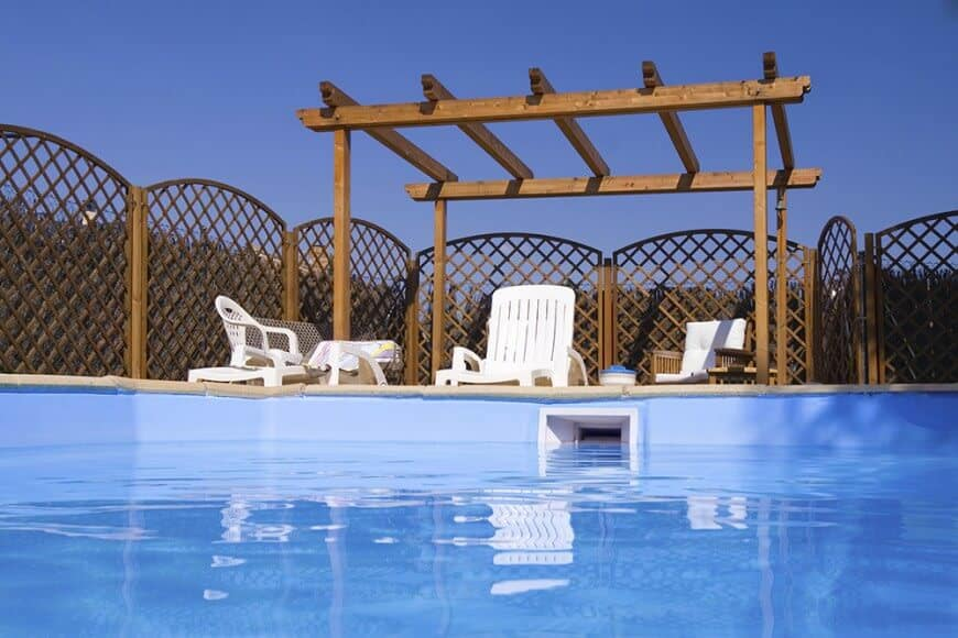 This pool-side pergola matches the wooden fence's finish for a unified look surrounding the swimming pool.