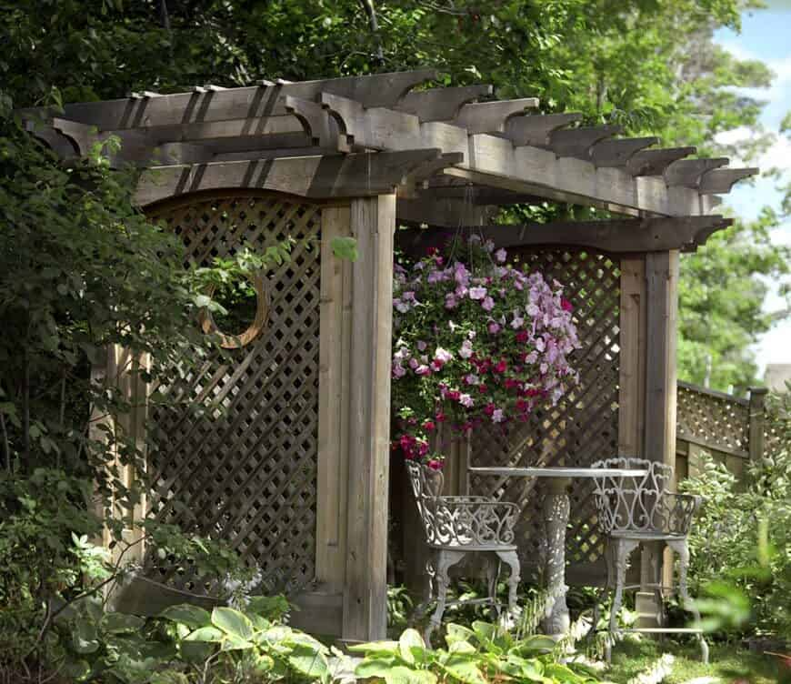 This pergola has lattice between its pillars that keep the space romantic. It is draped in bright flowers and makes a great garden sitting spot.