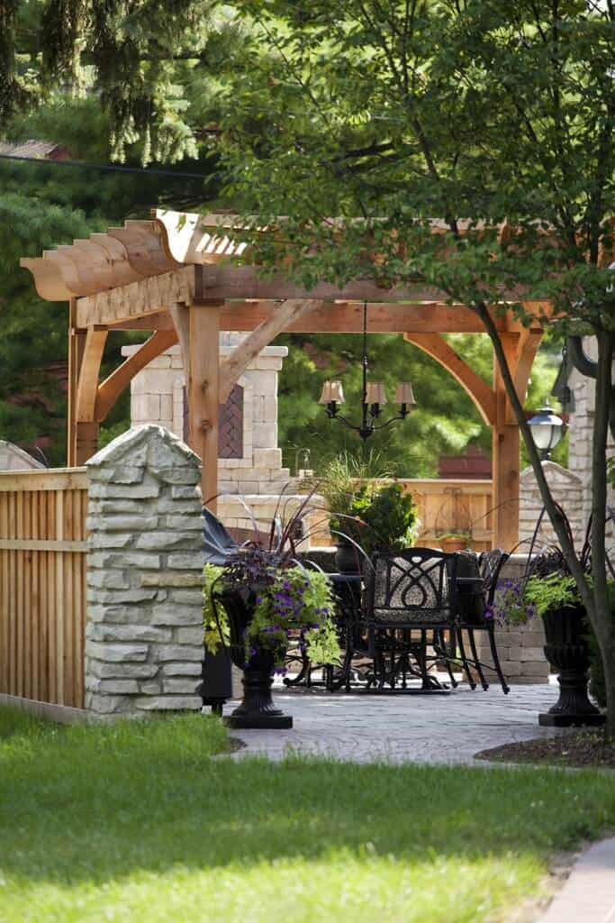 This all natural wooden pergola makes a gorgeous sitting area for the backyard patio. A lighting fixture hangs easily from it to make hassle free lighting in the yard.