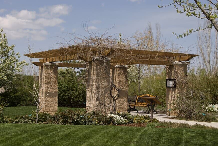 This pergola is much more rustic with stone pillars holding wide rafters. Bare vines climb up the stone and wrap around the rafters for a country atmosphere.