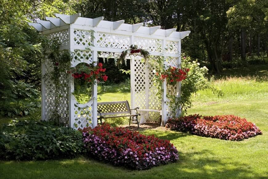 This pergola surrounded by blooming and colorful flowers is a perfect romantic spot in this garden area.