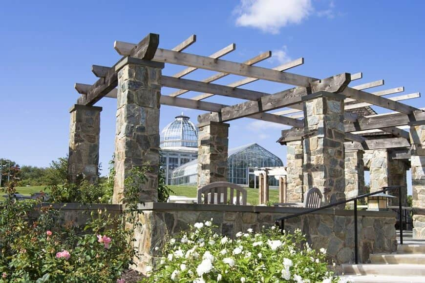 A traditional pergola featuring towering stone pillars and vintage rustic rafters.