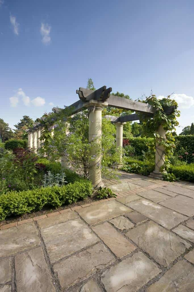 This pergola extends down a stone pathway as a bridge cover. Flowery vines trickle down it's pillars and into the green river below.