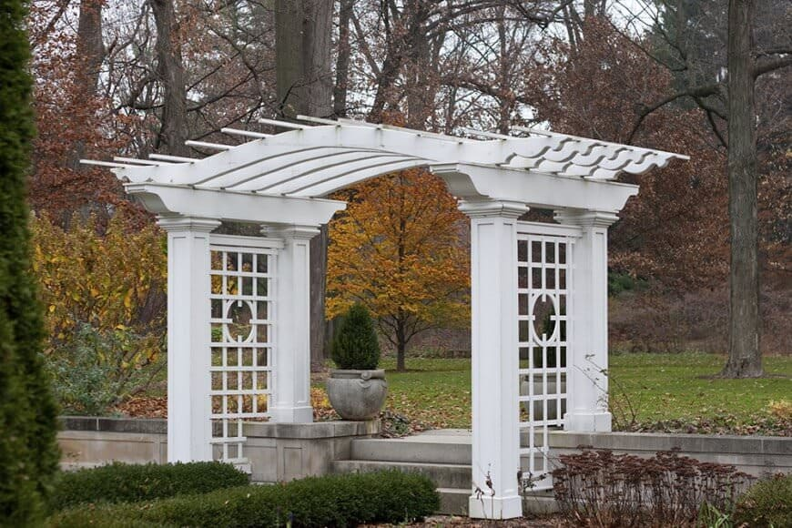 This romantic pergola is arched as a perfect addition to a walkway. It adds class to the steps leading upwards with it's magnificent egg shell color and lattice design.