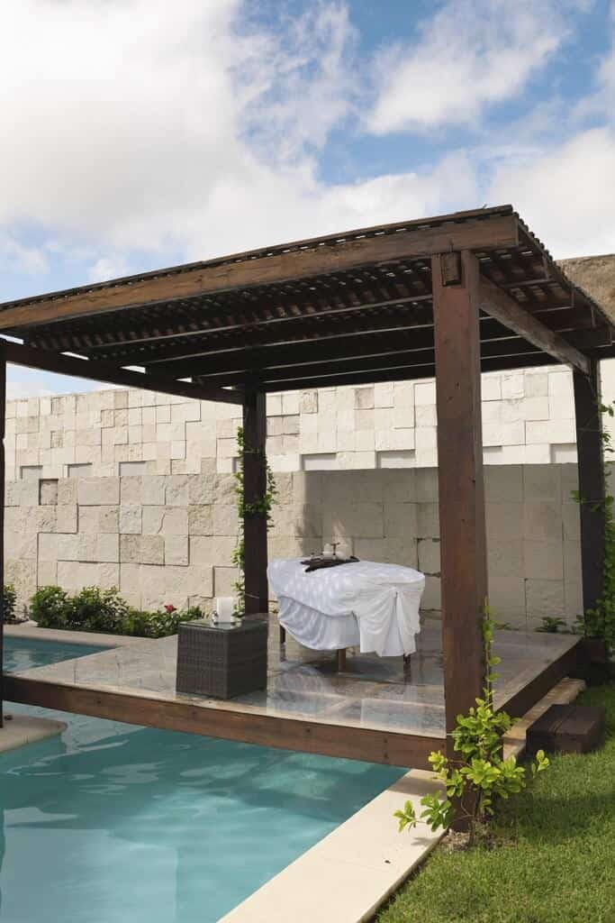 This pergola hangs over the edge of the pool. The rafters are topped with lattice while the wood features deep chocolate brown finish.