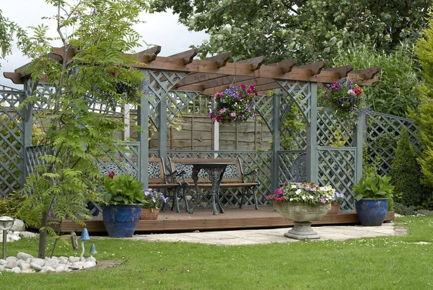 This pergola has been transformed from a simple outdoor structure to a magnificent patio. It's decorated in lattice and hanging flowers for a really beautiful finish.