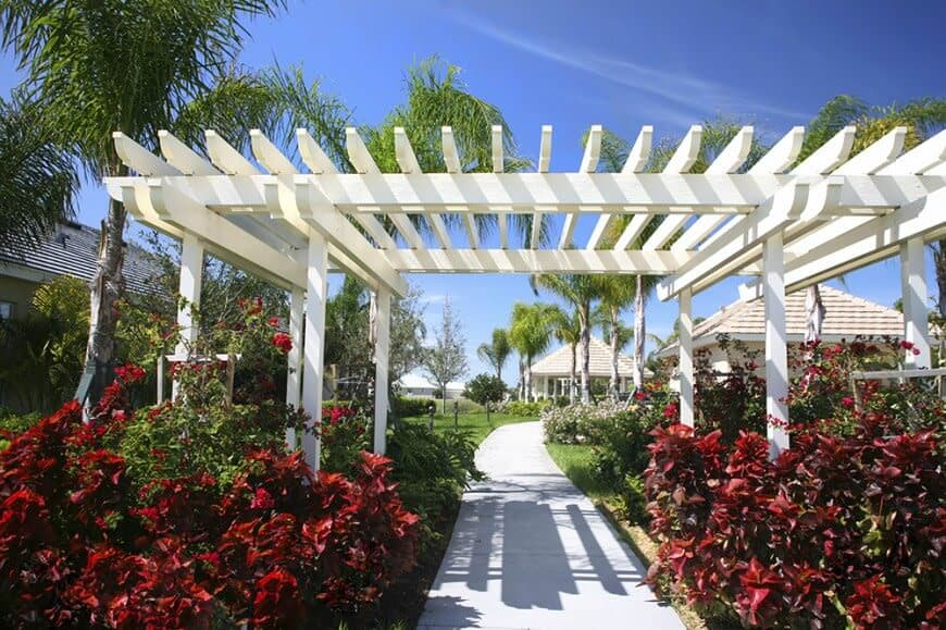 A white pergola surrounded by the beautiful greenery and red blooming flowers.