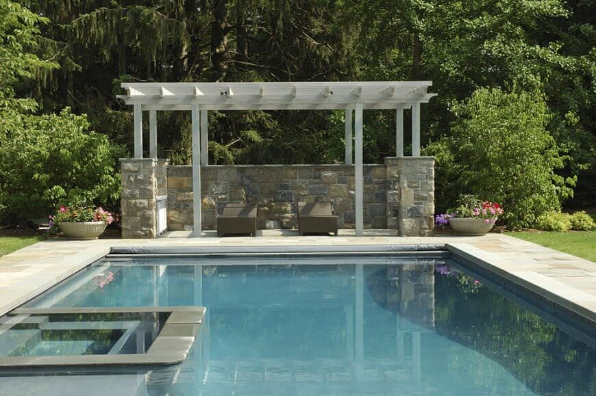 A pergola that uses a stone wall with the wooden pillars for an especially private sitting area. It adds a splash of color and privacy to the pool's lounging space.