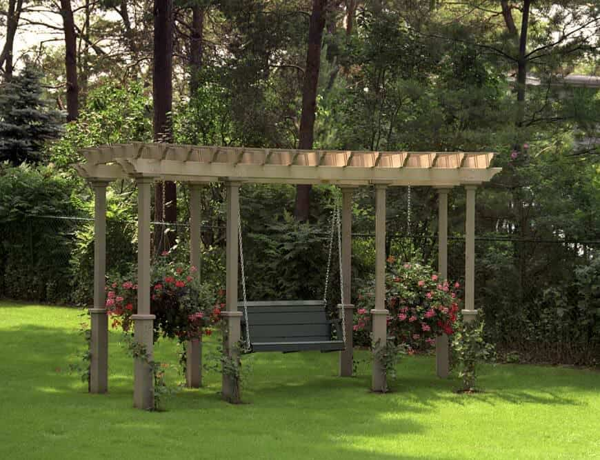 This stunning pergola styled into a garden swing holds petite vines and blossoming hanging flowers.