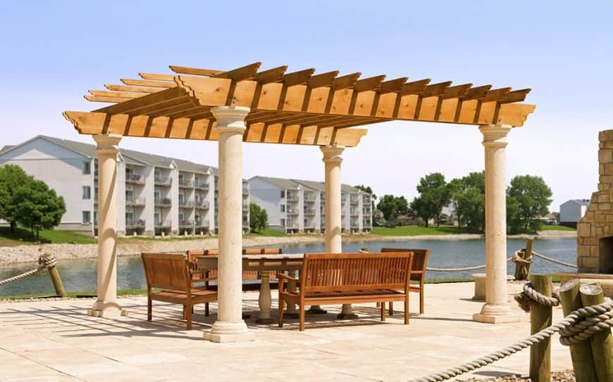 A pergola using a different colored stain for a bright pop against the tan pillars. The stain matches the wooden furniture for a unified appearance.