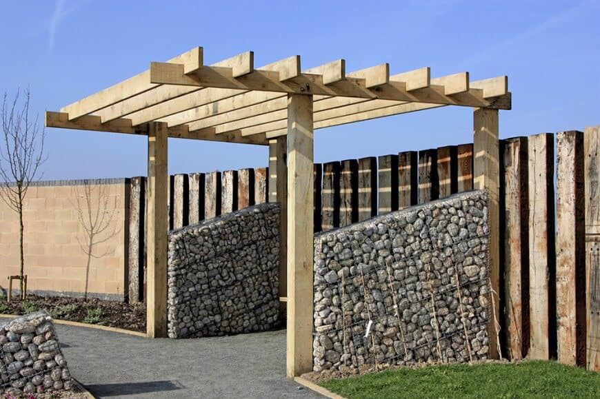 This pergola is simplified to fit the look of the rustic wooden fence. Between the pillars is stacked stone that adds a fluid movement from the driveway to the fence.