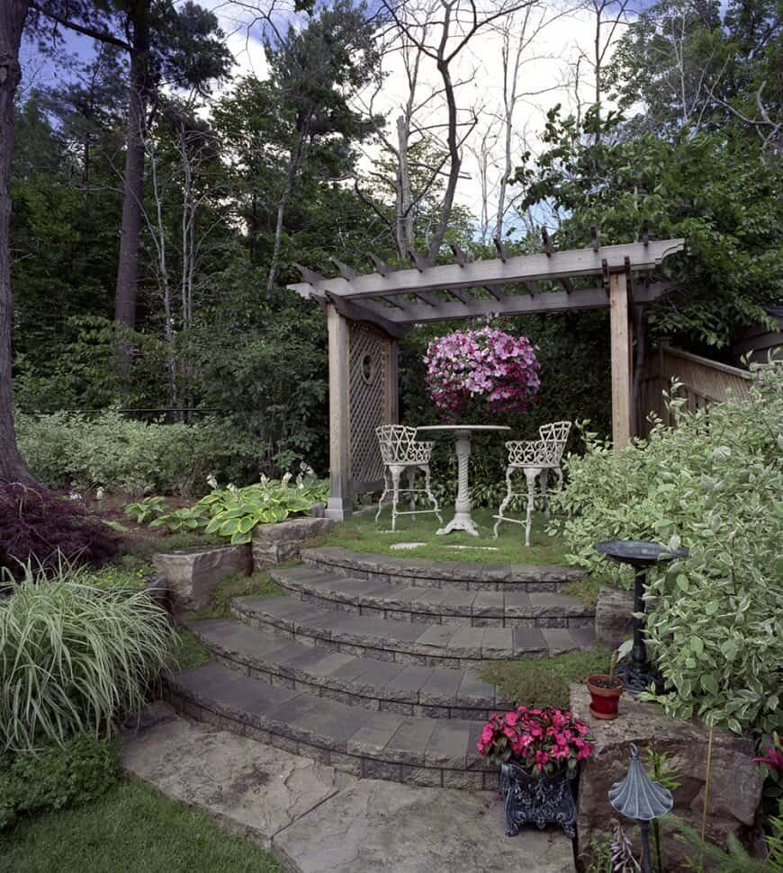 A gorgeous set of stone steps surrounded by flourishing bushes leads up to this garden pergola. The cottage pergola has a rustic wooden appearance with lattice on either side and a beautiful hanging flower pot.