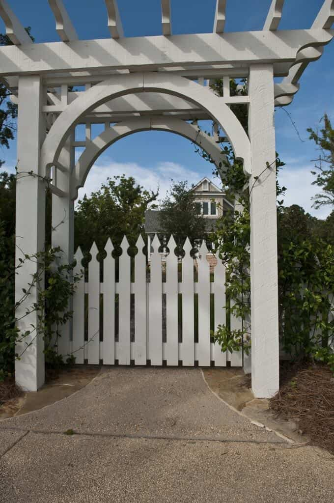 Instead of a large pergola used as a walkway, try a smaller one for an adorable gated entrance. This one has painted a soft cream color and has the perfect walkway to a home.
