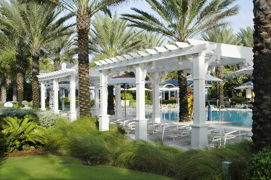 Pergolas can make a great poolside partner by looking classy on a patio. These cottage white pergolas cast a cool shade onto the seating without blocking the view of the pool and landscape.