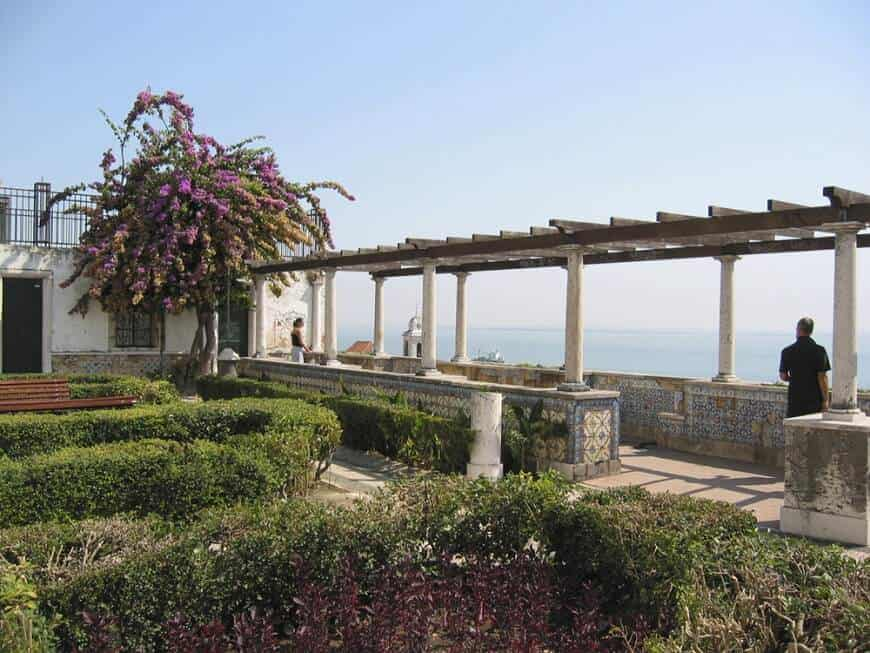 This pergola is held by handsome pillars and lines a gorgeous traditional walkway.