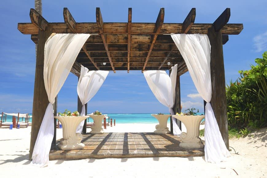 Pergolas make the perfect private patio as well. This darkly stained pergola holds breezy white curtains that can be pulled shut for some privacy on the beach.