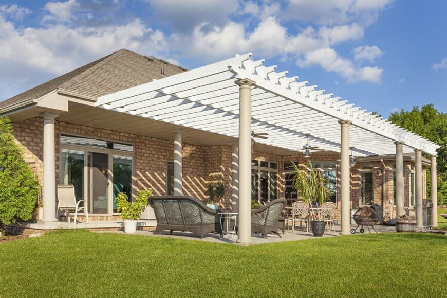 This bright white pergola stands tall as it acts as an awning for a summer patio. It shades the patio without completely blocking out the sun with it's spaced out rafters.