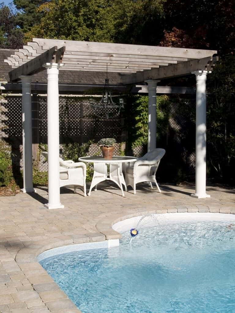 This poolside beauty looks absolutely stunning on the stone patio. The pergolas pillars match the white wicker furniture it keeps cool.