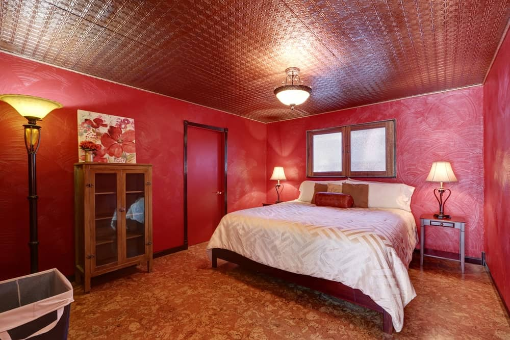 Medium-sized master bedroom boasting stunning red ceiling and flooring, along with red walls surrounding the classy bed setup lighted by table lamps on both sides.