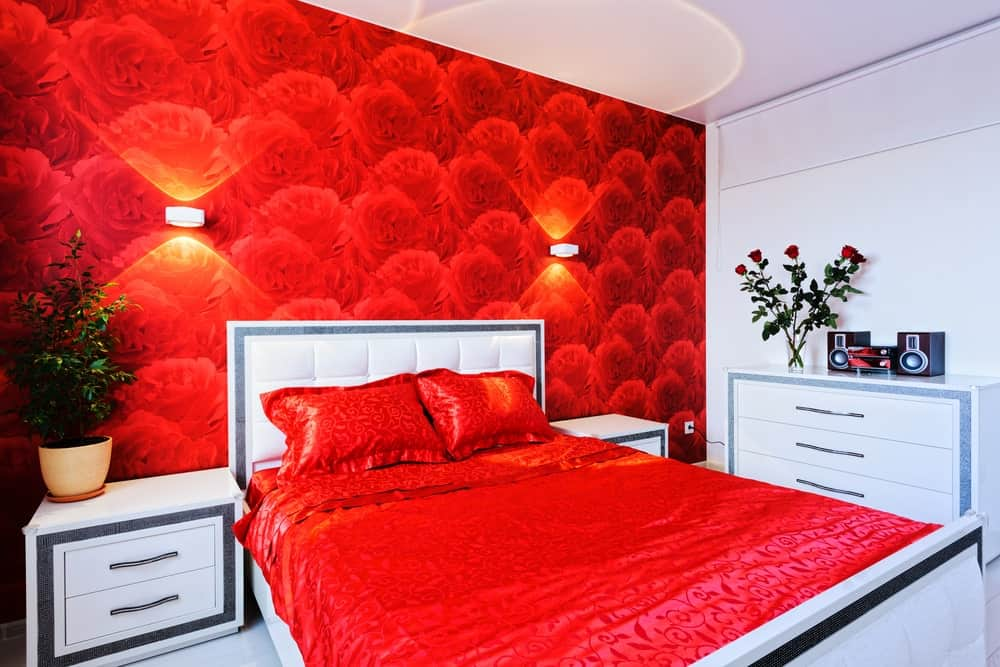 A focused shot at this master bedroom's red accent bed setup with a red roses decorated wall lighted by wall sconces.
