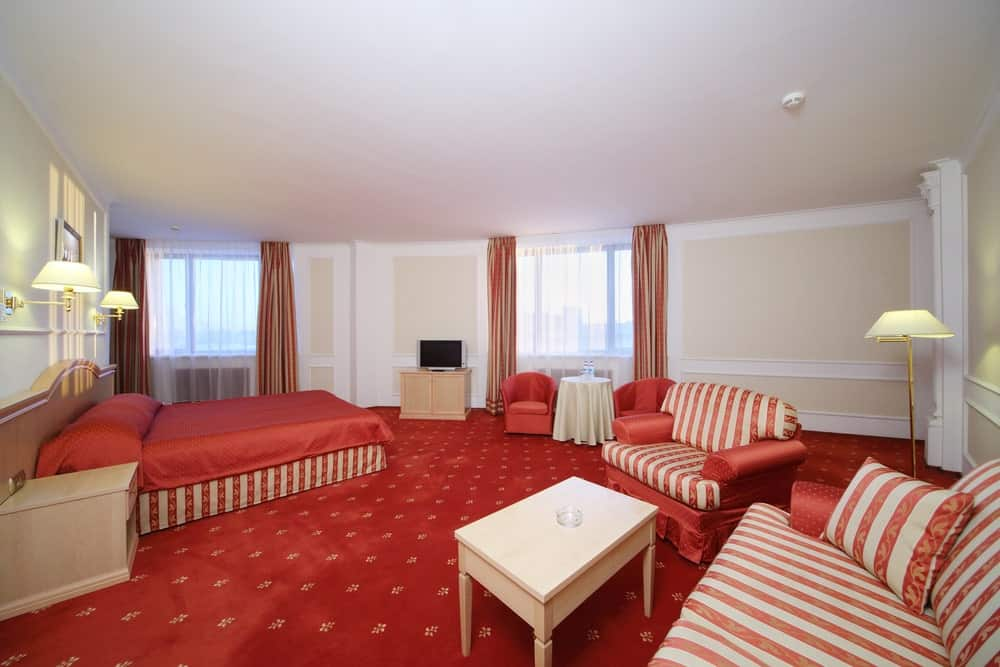 Large master bedroom featuring elegant decorated red carpet flooring. The room also offers a large red bed lighted by classy wall lights.