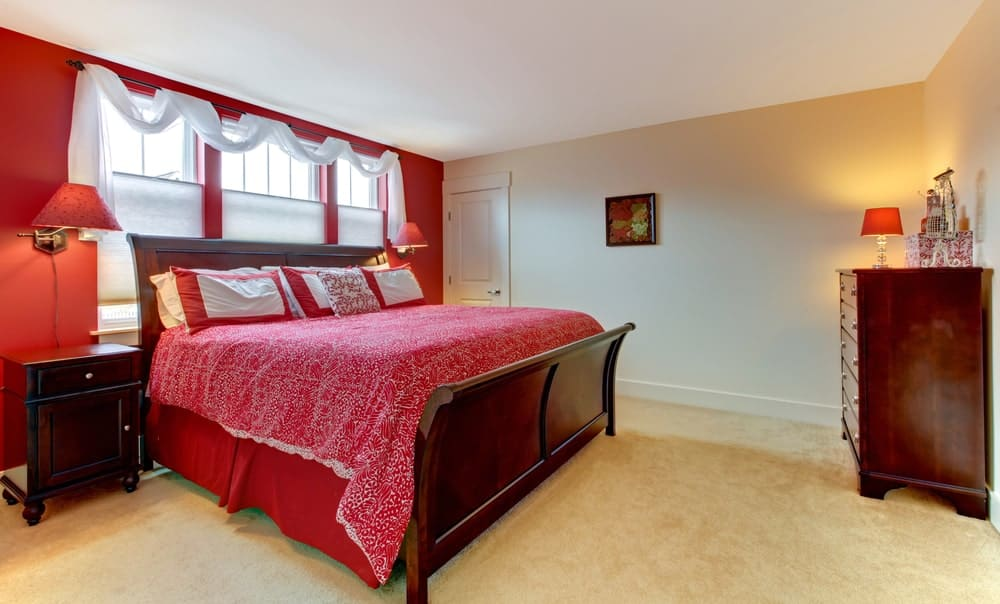 A master bedroom boasting a large elegant bed setup surrounded by red and white walls along with carpeted flooring.