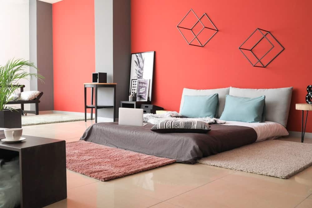 A spacious master bedroom with a cozy bed setup along with red walls with stylish 3D wall decors and large tiles flooring.