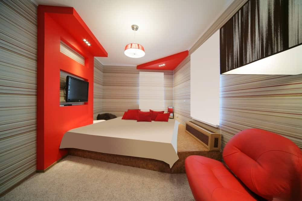 Contemporary master bedroom boasting a custom bed setup with a stylish red couch on the side and a widescreen TV set in front.