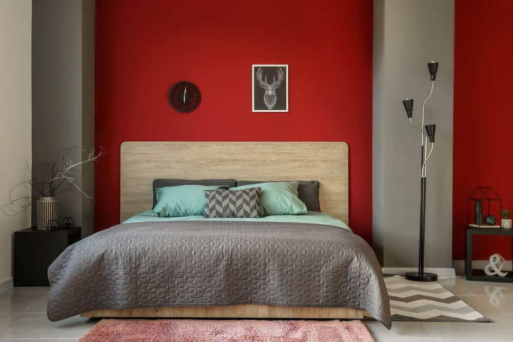 A focused shot at this master bedroom's modish bed setup surrounded by gray and red walls that look stunning together.