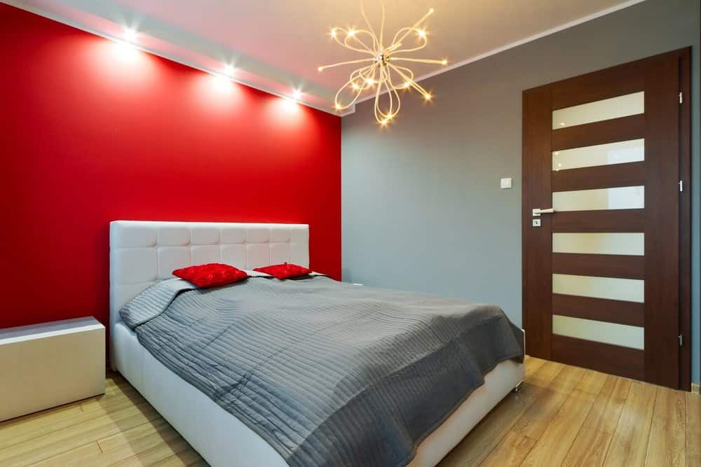 This master bedroom offers hardwood flooring and gray and red walls, lighted by bright ceiling lights and a gorgeous chandelier.
