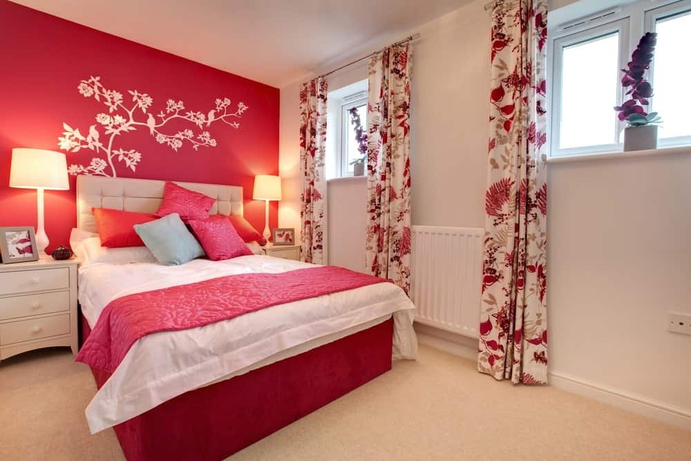 Master bedroom with a red wall with a decoration along with lovely red accent window curtains and bed setup lighted by table lamps.