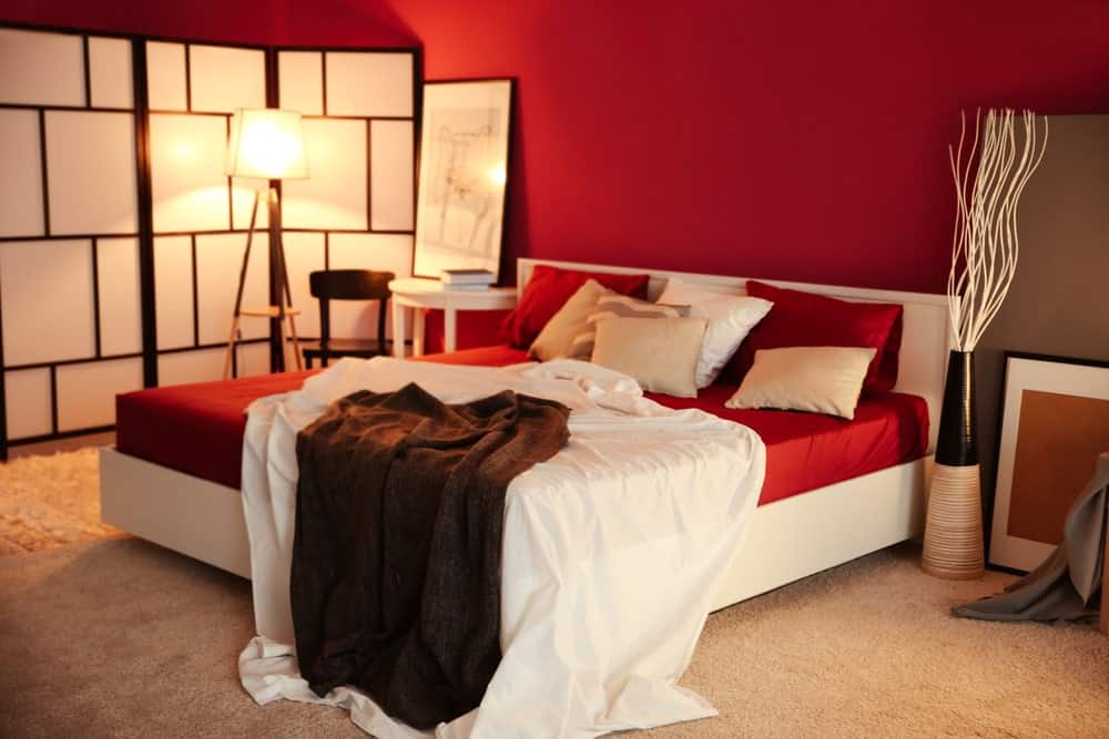 This master bedroom offers a red accent bed setup along with red walls and carpeted flooring.