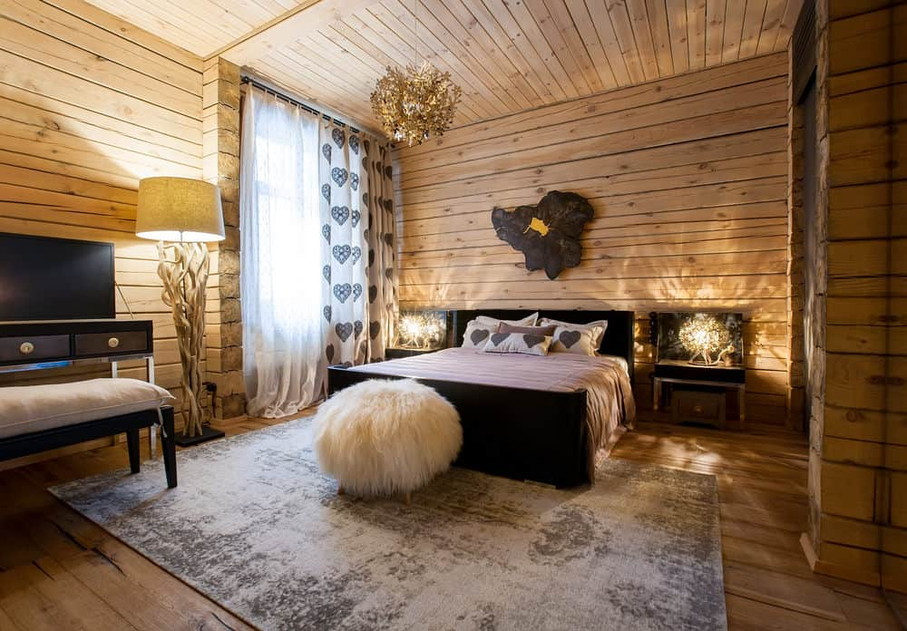 Rustic primary bedroom with a wooden ceiling, wooden walls and hardwood flooring topped by a stylish area rug. There's a modish bed setup lighted by fancy table lamps on both sides.