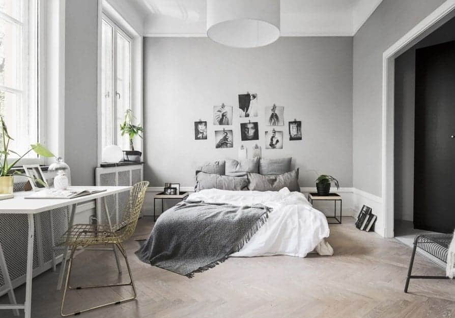 Scandinavian style primary bedroom with stylish herringbone-style hardwood flooring and a tall ceiling. It offers a modish gray bed and a study desk on the side, surrounded by gray walls.