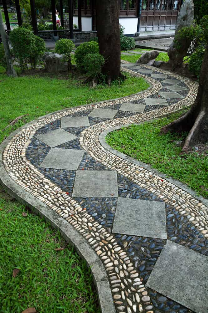 Intricately designed stone walkway features white and blue stones mapping out a space for large square grey slabs.