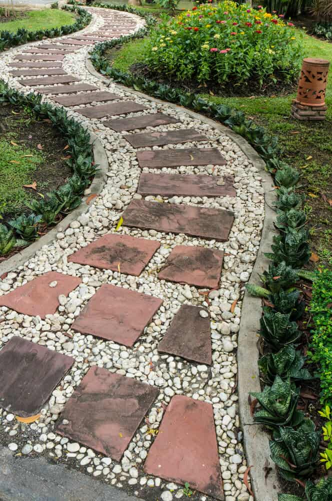 White pebble walkway features red flagstone steps, surrounded by concrete edging.