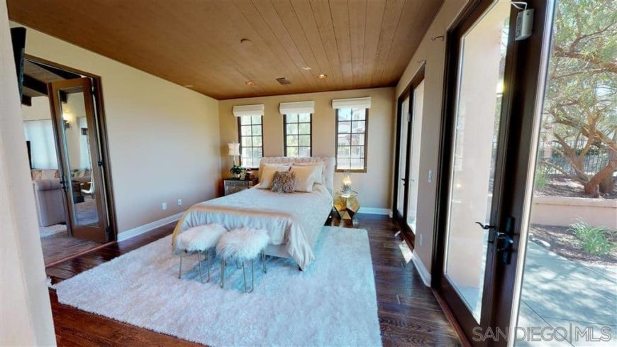 A Spanish-style primary bedroom with hardwood flooring topped by a white area rug, along with a wooden regular ceiling. There's a doorway leading to the home's outdoor area.