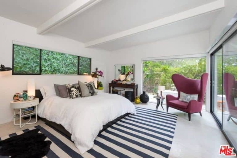 White master bedroom with a stylish blue and white striped rug. There's a luxurious chair with an enchanting side table.