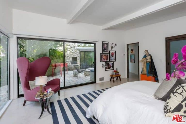 Ellen Pompeo's mid-century modern bedroom also features traditional wall decors and a large religious figurine.