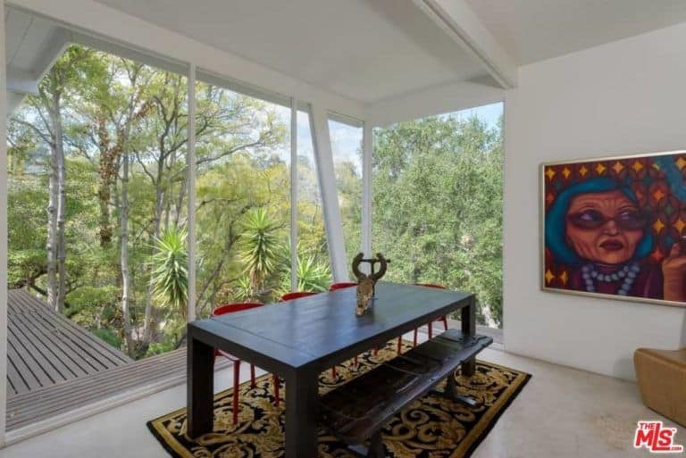 This dining room showcases a floor to ceiling windows where you can enjoy a majestic forest view. It includes a wooden dining table with a bench and red chairs that sit on a black patterned rug.