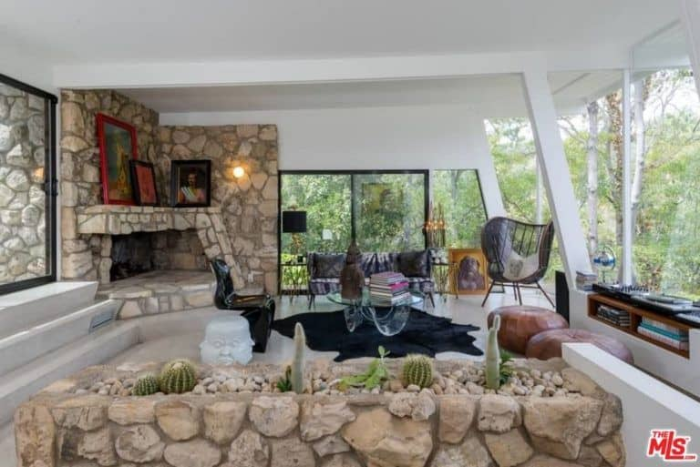 Clean white living room accented with a stone fireplace and planter filled with lovely succulents and pebbles. You can feel the serene ambiance of the enchanting forest through the full height glazing.