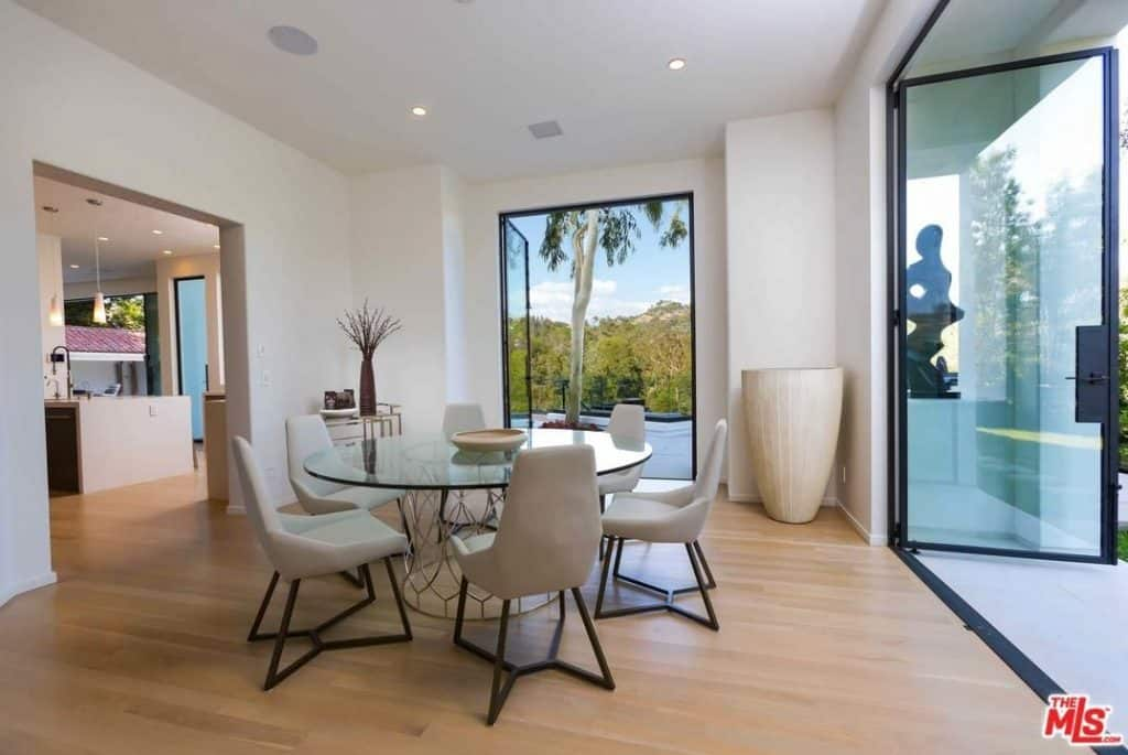 Dining room with a modern dining table set featuring a round glass top dining table and stylish chairs. There are doorways leading to the home's outdoor area.