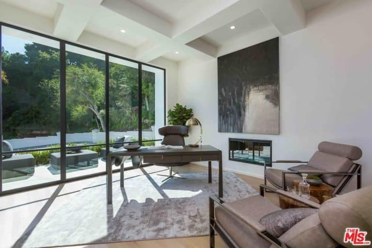 The office space filled with natural light from the floor-to-ceiling windows and overlooking the peaceful and private garden is a perfect spot in Eva Longoria's house that is a work from home inspiration.