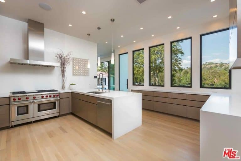 Spacious kitchen area featuring white walls and hardwood flooring. The ceiling is lighted by recessed lights and pendant lights.