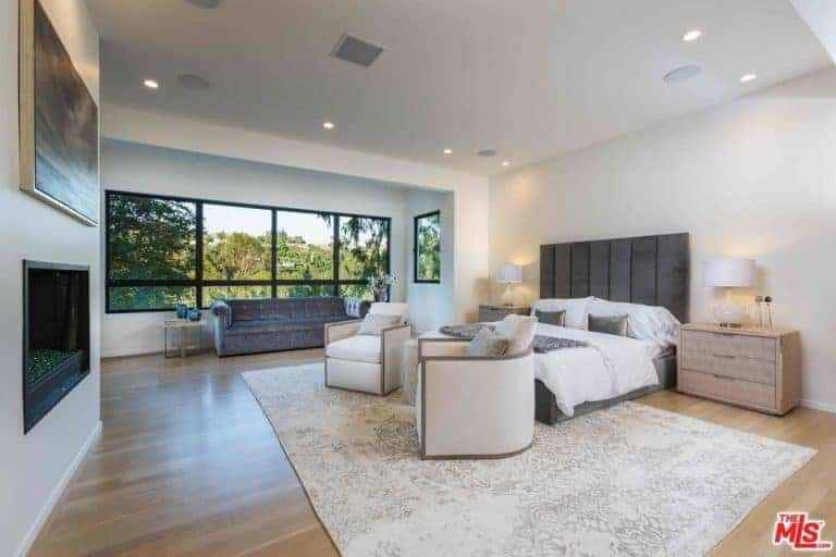 Large master bedroom with a long couch near the glass windows. The room boasts white walls and ceiling, along with a classy rug.