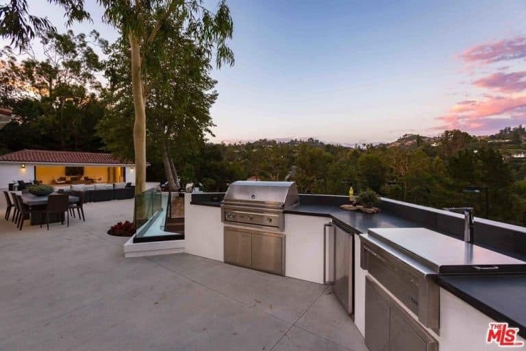 Modish outdoor kitchen with white finished bar counter with smooth black countertop.