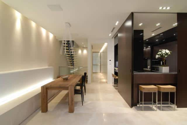 A dine-in kitchen with a dining table set with a bench seating. The ceiling lights are absolutely attractive.